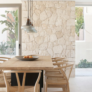 This is an example of a beach style dining room in Palma de Mallorca with beige walls and beige floors.