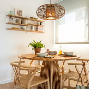 Modelo de comedor actual con paredes blancas, suelo de madera en tonos medios y suelo marrón