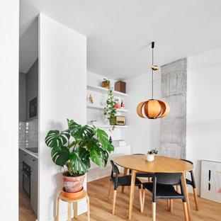 Modelo de comedor actual, abierto, con paredes blancas, suelo de madera clara y suelo beige