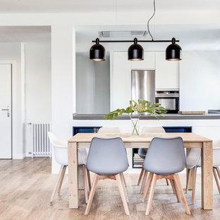 Diseño de comedor escandinavo, abierto, con paredes blancas, suelo de madera en tonos medios y suelo beige