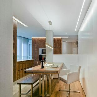 Modelo de comedor de cocina actual, de tamaño medio, sin chimenea, con paredes blancas y suelo de madera en tonos medios