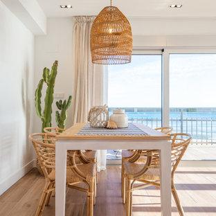 Imagen de comedor costero, de tamaño medio, abierto, con paredes blancas y suelo beige