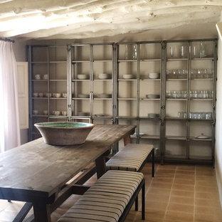 Idee per una grande sala da pranzo country chiusa con pareti beige, pavimento in terracotta, cornice del camino in metallo e camino classico