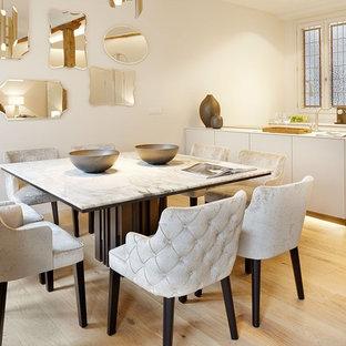 Imagen de comedor contemporáneo con paredes blancas, suelo de madera clara y suelo beige