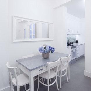 Diseño de comedor mediterráneo con paredes blancas, suelo de cemento y suelo gris