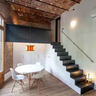 Modelo de comedor urbano, de tamaño medio, abierto, sin chimenea, con paredes blancas y suelo de madera en tonos medios