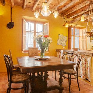 Modelo de comedor de cocina de estilo de casa de campo, sin chimenea, con paredes amarillas y suelo marrón