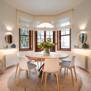 Immagine di una grande sala da pranzo aperta verso il soggiorno contemporanea con pavimento in laminato, nessun camino, pavimento marrone e pareti bianche