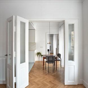 Modelo de comedor vintage, de tamaño medio, cerrado, con paredes blancas, suelo de madera en tonos medios y suelo marrón