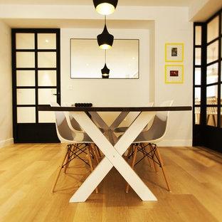 Imagen de comedor actual, de tamaño medio, cerrado, sin chimenea, con paredes blancas y suelo de madera en tonos medios