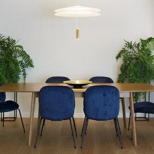 Modelo de comedor actual con paredes blancas, suelo de madera en tonos medios y suelo beige