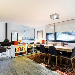 Immagine di una sala da pranzo aperta verso il soggiorno minimal di medie dimensioni con pareti bianche e camino sospeso