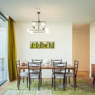 Imagen de comedor retro con paredes blancas, suelo de madera en tonos medios y suelo marrón