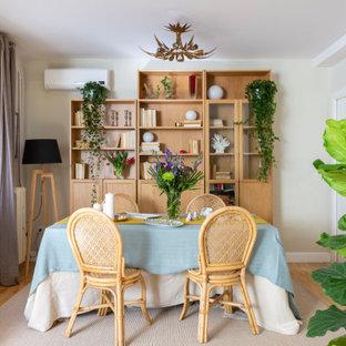 Modelo de comedor ecléctico con paredes blancas, suelo de madera en tonos medios y suelo marrón