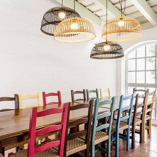 Inspiration pour une salle à manger méditerranéenne avec un mur blanc, un sol en carreau de terre cuite et un sol orange.