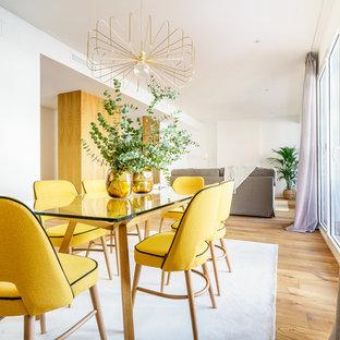 Diseño de comedor actual, de tamaño medio, abierto, con paredes blancas, suelo de madera en tonos medios y suelo marrón