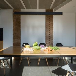 Imagen de comedor urbano con paredes blancas y suelo gris