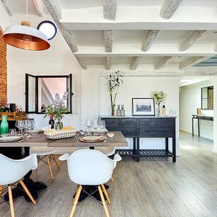 Imagen de comedor mediterráneo con paredes blancas, suelo de madera en tonos medios y suelo gris