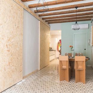 Immagine di una sala da pranzo aperta verso il soggiorno shabby-chic style di medie dimensioni con pareti verdi, pavimento in cemento e pavimento beige
