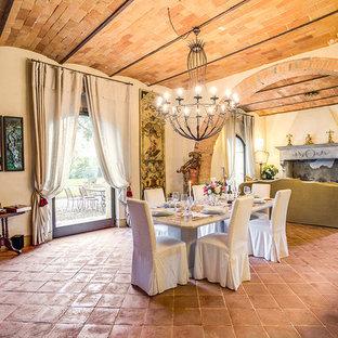 Idée de décoration pour une salle à manger ouverte sur le salon méditerranéenne avec un mur beige, un sol en carreau de terre cuite, une cheminée standard, un manteau de cheminée en plâtre et un sol orange.