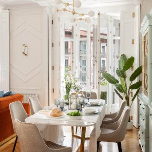 Offenes Modernes Esszimmer mit weißer Wandfarbe, hellem Holzboden, braunem Boden und Wandpaneelen in Sonstige