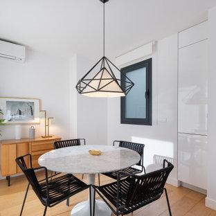 Foto de comedor de cocina panelado, nórdico, de tamaño medio, panelado, con paredes blancas, suelo de madera clara, suelo beige y panelado