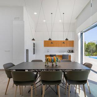 Ejemplo de comedor actual, abierto, con paredes blancas y suelo gris