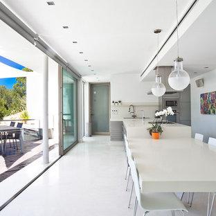 Ejemplo de comedor de cocina contemporáneo con paredes blancas y suelo blanco