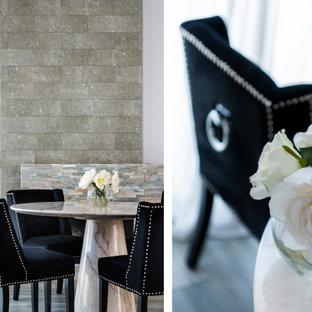 Cette photo montre une grand salle à manger ouverte sur le salon tendance avec un mur blanc, un sol en carrelage de porcelaine, une cheminée standard, un manteau de cheminée en pierre de parement, un sol gris et un mur en parement de brique.