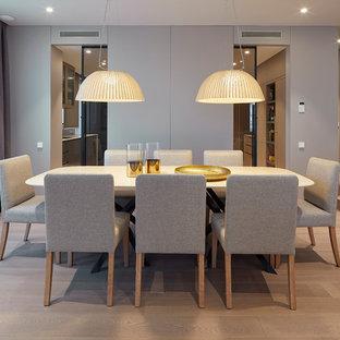 Diseño de comedor contemporáneo, sin chimenea, con paredes grises, suelo de madera clara y suelo beige