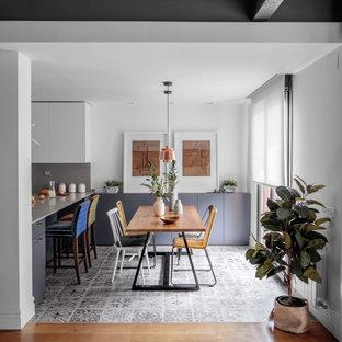 Imagen de comedor de cocina actual, de tamaño medio, con paredes blancas y suelo gris