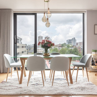 This is an example of a contemporary dining room in London with grey walls, light hardwood flooring and beige floors.