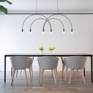 Immagine di una grande sala da pranzo aperta verso il soggiorno minimalista con pareti bianche, pavimento con piastrelle in ceramica e pavimento beige