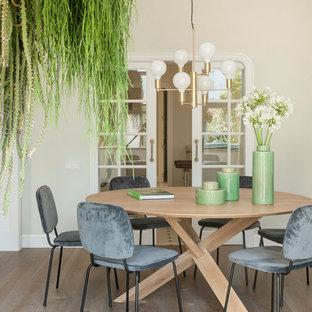 Imagen de comedor romántico, sin chimenea, con suelo de madera en tonos medios y paredes beige