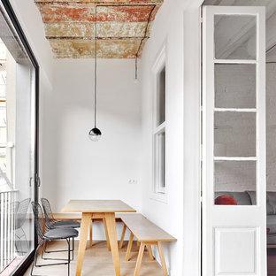 Modelo de comedor actual, cerrado, sin chimenea, con paredes blancas, suelo de madera clara y suelo beige
