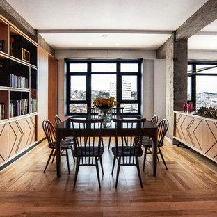 Imagen de comedor actual, extra grande, abierto, con paredes blancas, suelo de madera en tonos medios y suelo marrón