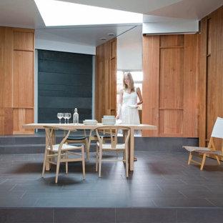 Ejemplo de comedor actual, de tamaño medio, con paredes marrones, suelo de baldosas de porcelana y suelo gris
