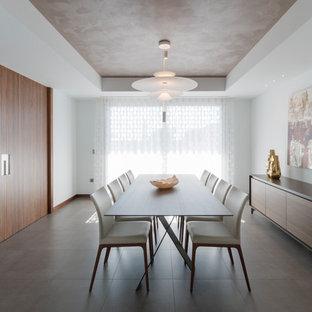 Modelo de comedor actual, grande, cerrado, con paredes blancas y suelo gris