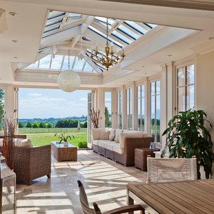 Réalisation d'une grand véranda tradition avec un sol en travertin, aucune cheminée et un plafond en verre.