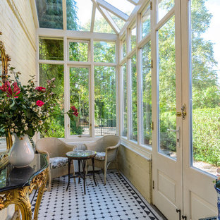 This is an example of a small victorian sunroom in Belfast with a glass ceiling, no fireplace and multi-coloured floor.