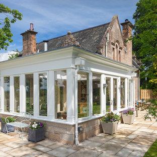 Inspiration för stora klassiska uterum, med travertin golv, en öppen vedspis, en spiselkrans i gips, takfönster och beiget golv