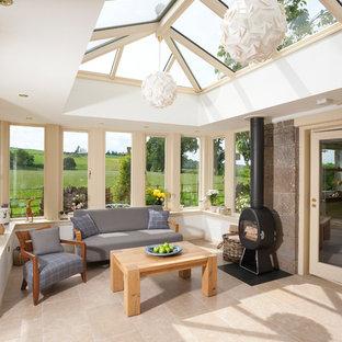 Aménagement d'une grand véranda classique avec un sol en travertin, un poêle à bois, un manteau de cheminée en plâtre, un puits de lumière et un sol beige.