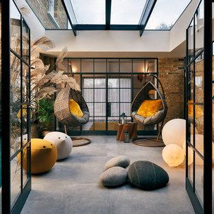 Großer Moderner Wintergarten mit Porzellan-Bodenfliesen, Glasdecke und grauem Boden in London