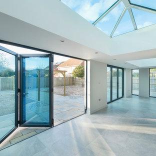 Inspiration pour une grand véranda design avec un sol en carrelage de céramique et un plafond en verre.