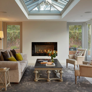 Design ideas for a classic conservatory in London with a skylight, a ribbon fireplace and a stone fireplace surround.