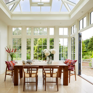 This is an example of a medium sized traditional conservatory in London with marble flooring, beige floors and a glass ceiling.