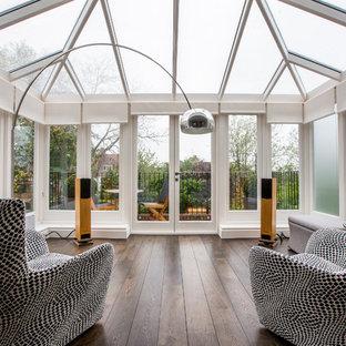 Aménagement d'une véranda contemporaine de taille moyenne avec un sol en bois foncé, aucune cheminée et un plafond en verre.