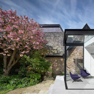 Inspiration for a small contemporary conservatory in Manchester with slate flooring, a glass ceiling and grey floors.