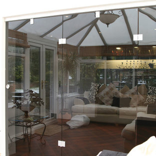 This is an example of a contemporary conservatory in Other with medium hardwood flooring and a glass ceiling.
