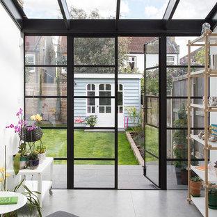 Idées déco pour une petit véranda scandinave avec aucune cheminée, un plafond en verre, béton au sol et un sol gris.